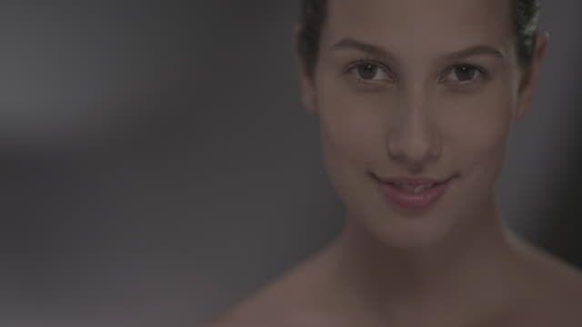 Woman looking up at camera and smirks.