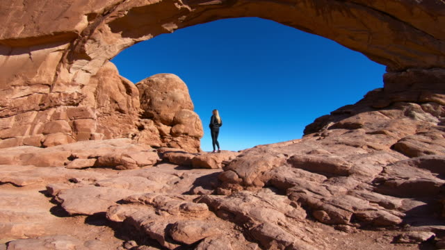 woman looking up, standing under arch, Arches National Park