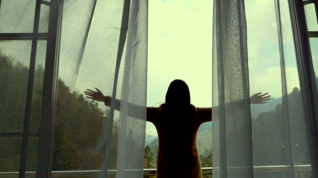 woman lookinng through window with arms raised - waving stock videos & royalty-free footage
