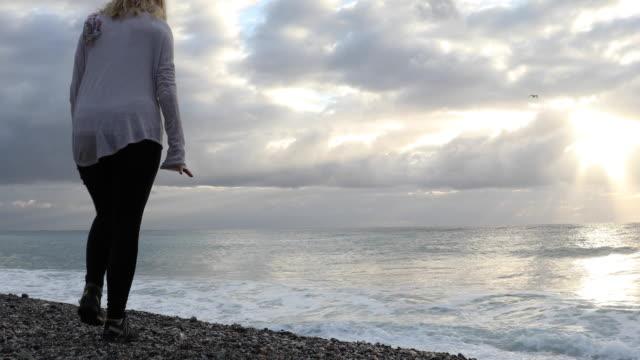 vídeos y material grabado en eventos de stock de woman looks across sea from empty beach, sunrise - una sola mujer madura