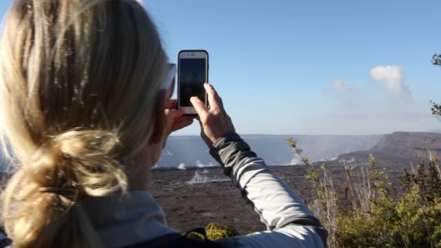 woman looks across volcanic landscape, takes smart phone pic - environmentalist stock videos & royalty-free footage