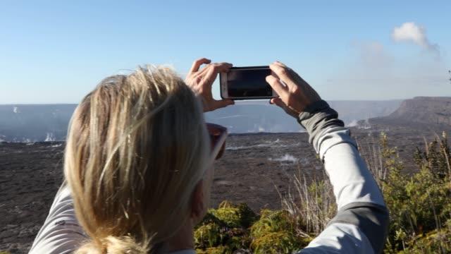 stockvideo's en b-roll-footage met vrouw kijkt over vulkanische landschap, neemt slimme telefoon pic - one mature woman only