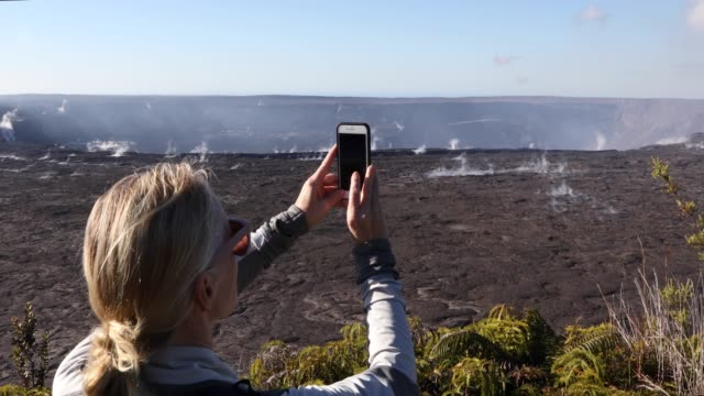 woman looks across volcanic landscape, takes smart phone pic - see other clips from this shoot 56 stock videos & royalty-free footage