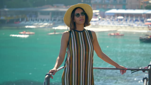 A woman looks at a Mediterranean Sea beach club in a luxury resort town in Italy, Europe. - Slow Motion