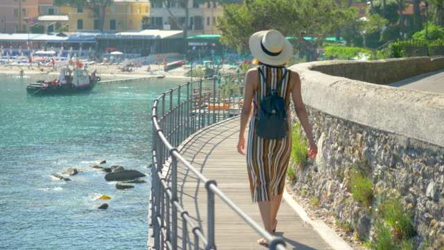 a woman looks at a mediterranean sea beach club in a luxury resort town in italy, europe. - slow motion - coastal feature stock videos & royalty-free footage