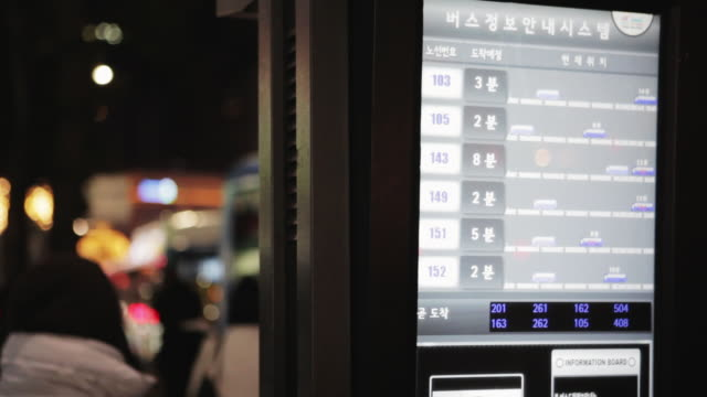 LS R/F Woman looks at electronic bus info system at bus stop in central Seoul / Seoul, South Korea