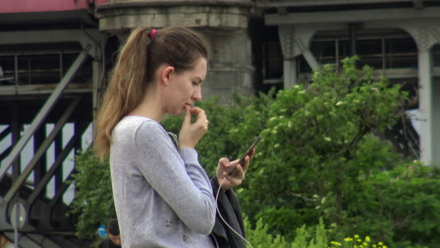 a woman looks at her mobile phone by the bank of the vistula river on may 28 2019 local authorities have sent sms's to city inhabitants to warn them... - other stock videos and b-roll footage