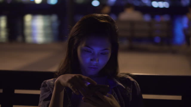 woman looks at her phone on park bench, panning shot - ベンチ点の映像素材/bロール