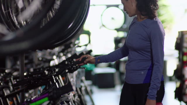 woman looks for new bicycle in local retail shop - sports equipment stock videos & royalty-free footage