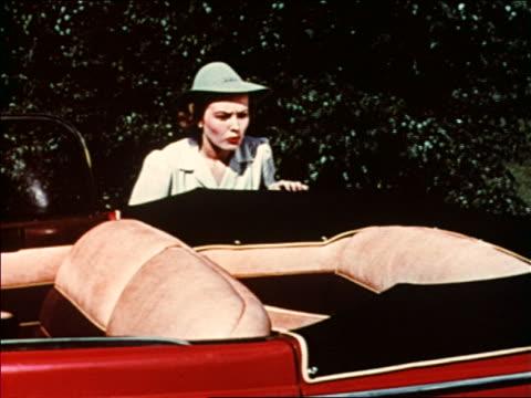 stockvideo's en b-roll-footage met 1941 woman looks in surprise at back seat of convertible packard / man joins her / industrial /audio - passagiersstoel