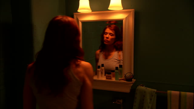 stockvideo's en b-roll-footage met a woman looks into a bathroom mirror, pulls her hair back, then leaves. - naderen