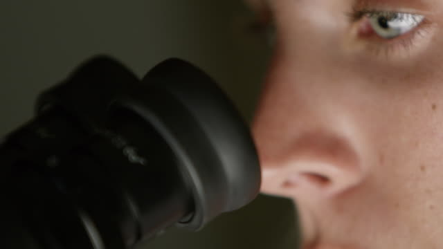 cu a woman looks into a microscope in a laboratory - scoperta video stock e b–roll
