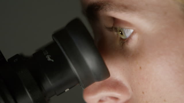 stockvideo's en b-roll-footage met cu a woman looks into a microscope in a laboratory - onderzoek