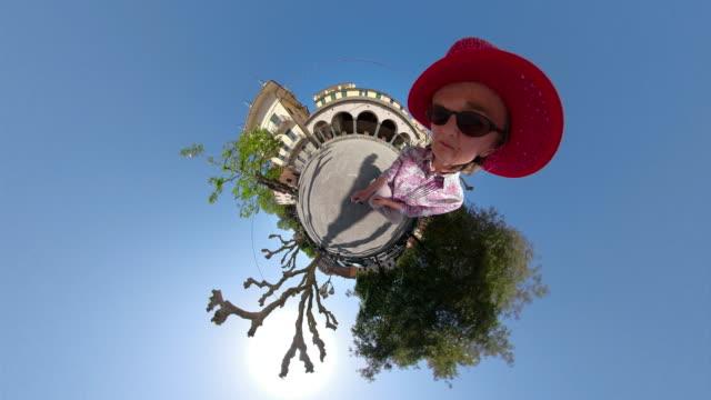 vidéos et rushes de woman looks into camera and move away with little planet effect - vidéo portrait