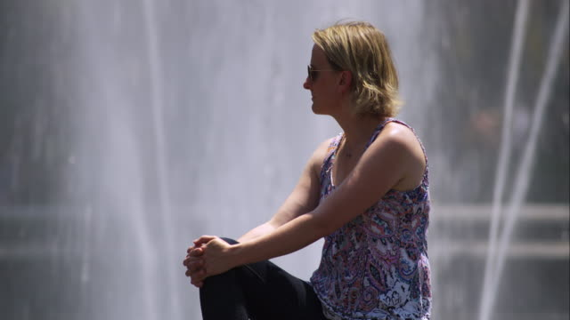 Woman looks off frame while sitting next to fountain in Washington Square Park.