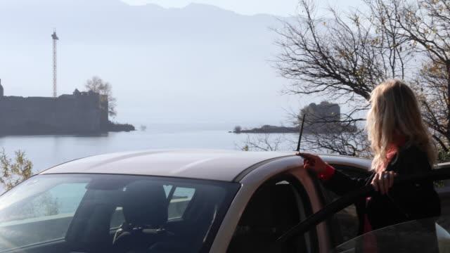 stockvideo's en b-roll-footage met vrouw ziet af van langs de weg naar verre kasteel, lake - alleen oudere vrouwen