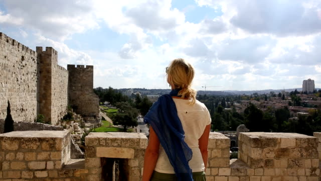Woman looks off to old wall and city, Jerusalem, Israel
