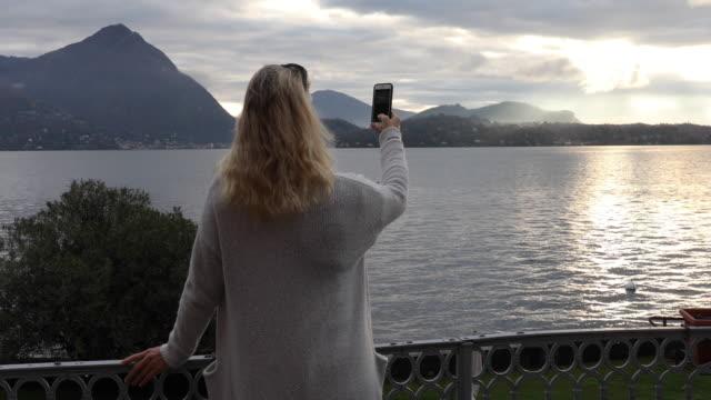 vidéos et rushes de la femme regarde dehors à travers le lac au lever de soleil - photophone
