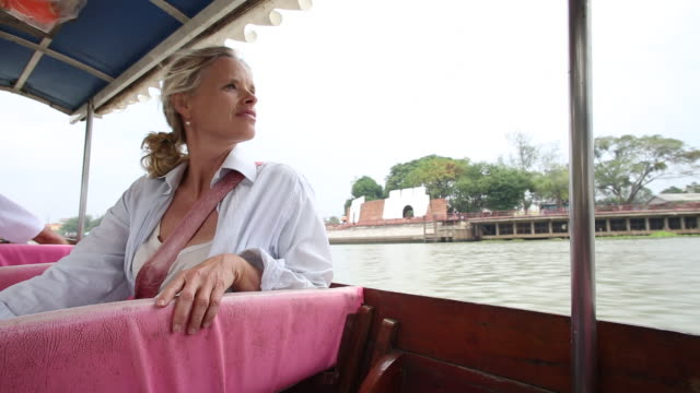 Woman looks out across river on long tail boat ride