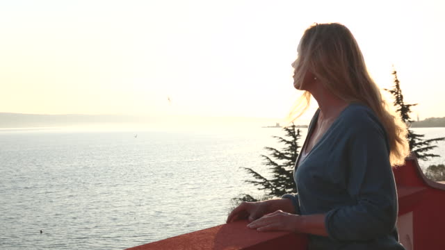 Woman looks out across sea from railing