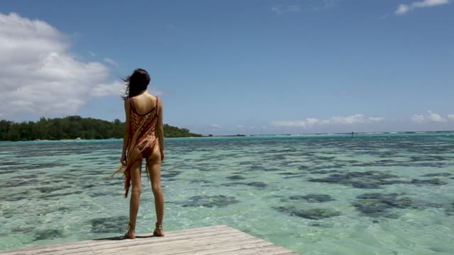 vidéos et rushes de woman looks out at ocean from tahiti dock, handheld - polynésie française