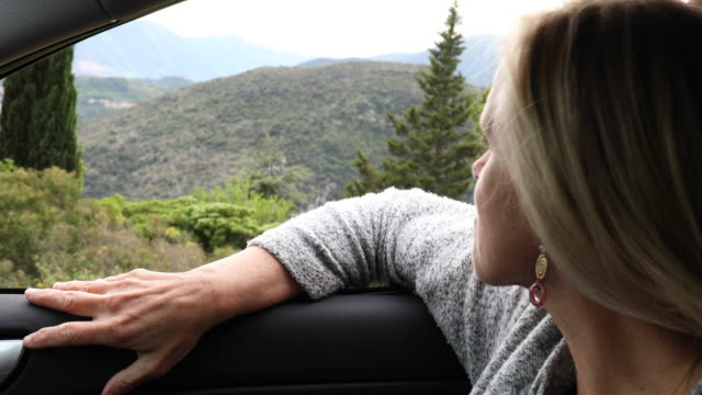 woman looks out at view from car, hills below - top video stock e b–roll