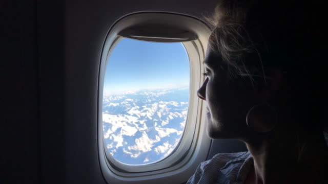 Woman looks out of airplane window over alps