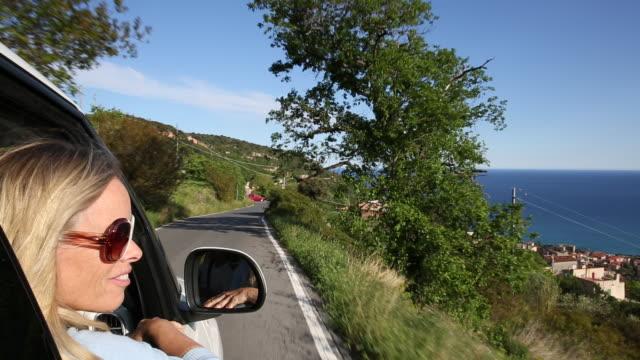 woman looks out of car passenger window, over sea - solo una donna di età media video stock e b–roll