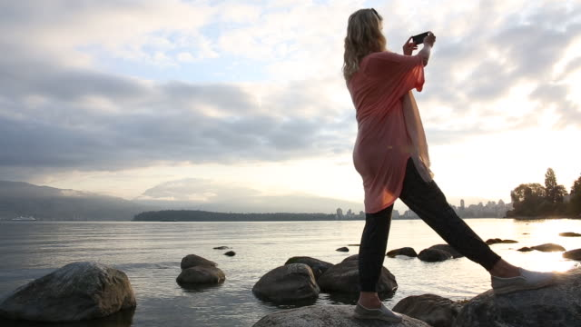 woman looks out to city from tidal rocks - tunic stock videos & royalty-free footage