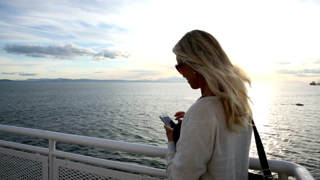 woman looks out to sea from deck of ship, takes picture - ferry deck stock videos & royalty-free footage