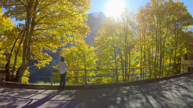 女性が太陽に向かって道路から見える - 中年の女性一人点の映像素材/bロール