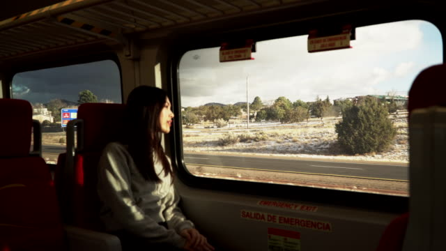 vidéos et rushes de woman looks out train car window, new mexico - dedans