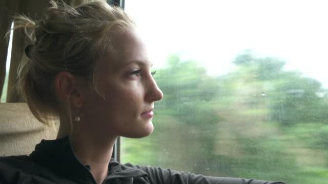 女性が移動列車の窓の外に見える