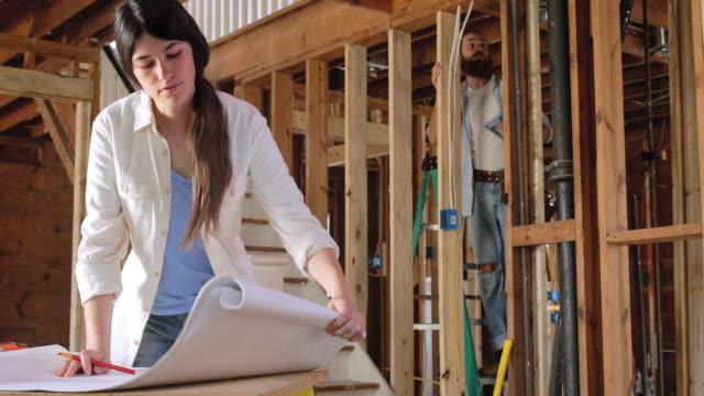vídeos y material grabado en eventos de stock de woman looks over blueprints as man works on home renovations in background - reforma