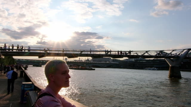 woman looks over the london cityscape along the thames river at sunset in london, england, at sunset. - naga river stock videos and b-roll footage