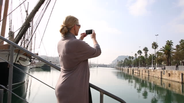 woman looks past marina to historic center, takes pic - see other clips from this shoot 56 stock videos & royalty-free footage
