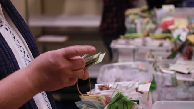 woman looks through free packages of gardening seeds during the seed and supply swap at mother hubbard's cupboard, monday, february 18, 2019 in... - sachet stock videos & royalty-free footage