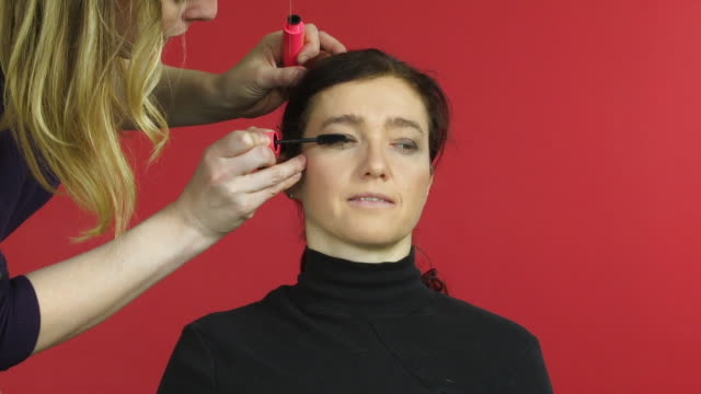 woman looks to camera whilst makeup artist applies eyelash makeup - sideways glance stock videos & royalty-free footage