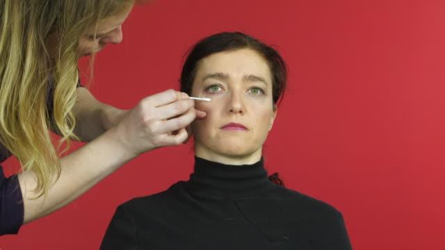vídeos de stock, filmes e b-roll de woman looks to camera whilst makeup artist brushes her eyebrows - batom rosa