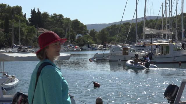Woman looks to sailing boats in marina of Vrboska