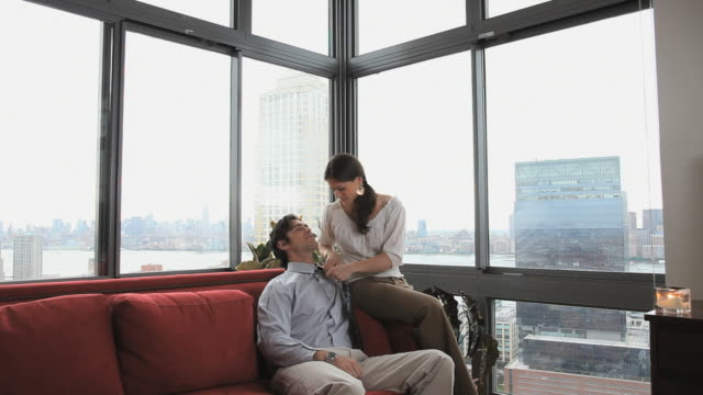ms woman loosening man's tie then kissing him sitting on sofa, jersey city, new jersey, usa - tie stock videos and b-roll footage