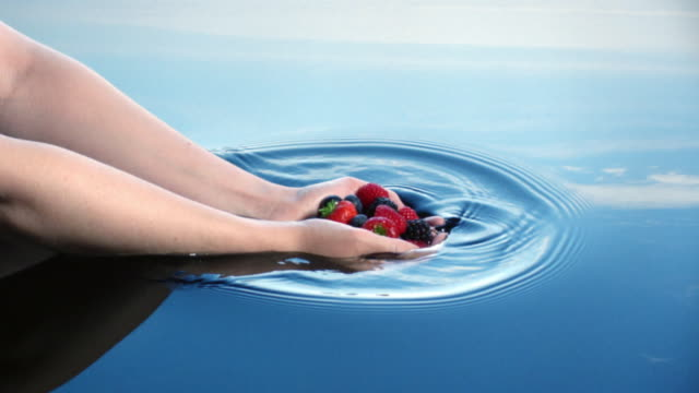 A woman lowers a handful of fruit into water leaving ripples reflected in a blue sky.
