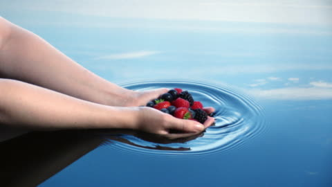 stockvideo's en b-roll-footage met a woman lowers a handful of fruit into water leaving ripples reflected in a blue sky.  - inslag