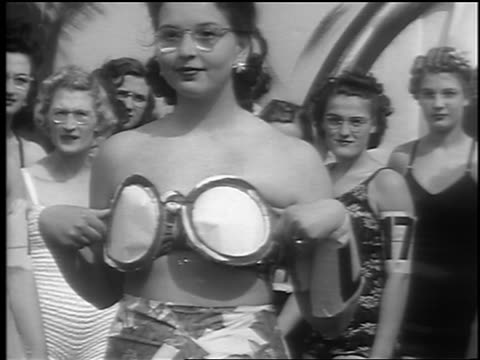 vidéos et rushes de b/w 1941 woman lowers large paper eyeglasses / reveals bikini top / smiles palisades park nj - concurrent