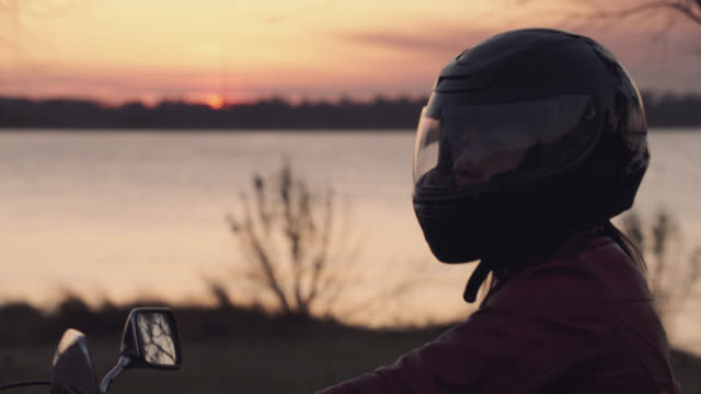 Woman lowers visor on helmet and takes off on motorcycle as sun sets over river.