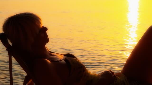 vídeos de stock, filmes e b-roll de hd dolly: mulher deitada no pôr-do-sol - espreguiçadeira