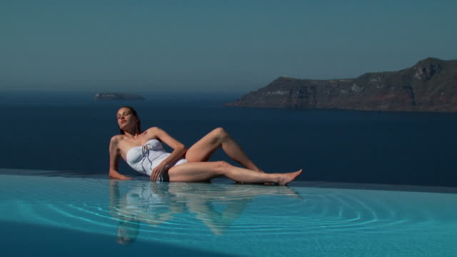 a woman lying at the edge of an infinity pool - infinity pool stock videos & royalty-free footage