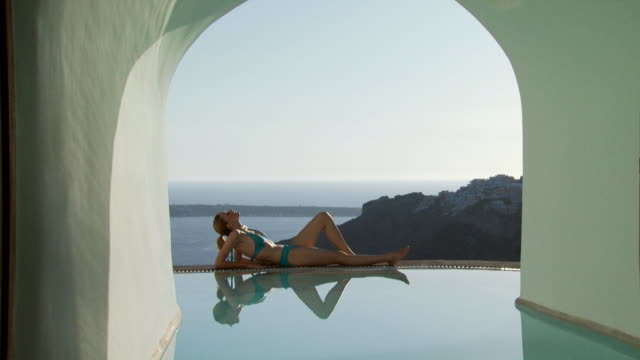 A woman lying by a luxurious pool
