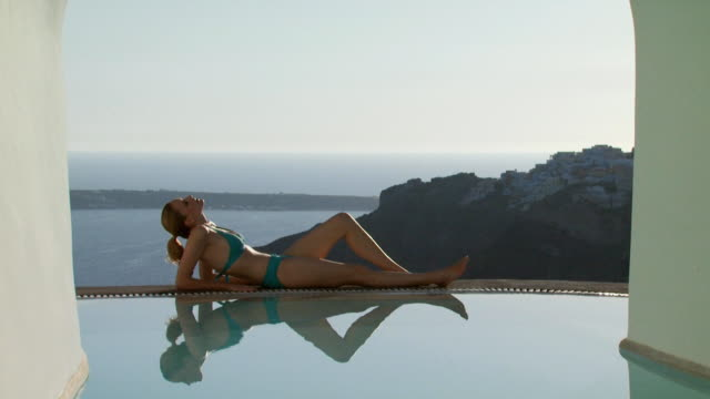 a woman lying by a luxurious pool - see other clips from this shoot 1144 stock videos & royalty-free footage