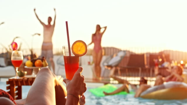 SLO MO Woman lying by the pool with a cocktail in her hand while other people dance in and around the pool at sunset
